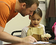 Jessee Burns (from left) goes over some instructions with his daughter, Alyse Burns, 5, both of Marion as she works on a carving of a dog during a meeting of the Cedar Valley Woodcarvers in Midway on Saturday, May 25, 2013.