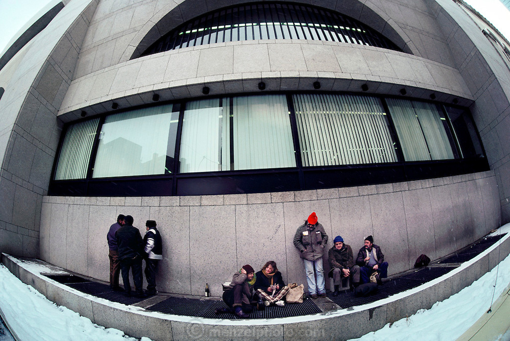 Group of homeless people in Boston in winter, keeping warm on a ventilation grill by the Boston Public Library.  New England, USA.