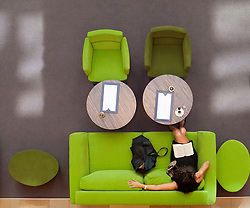 Woman reading on colorful sofa in atrium of upmarket shopping mall on Friedrichstrasse in Berlin Germany