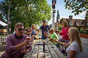 A group of people sit around a table and cheers a drink outside the The Flying Horse Pub, Cage Land, Smarden, Kent, England, UK.  (photo by Andrew Aitchison / In pictures via Getty Images)