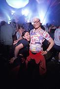 An oriental couple looking pleased on the dancefloor, Creamfields, UK 2000's