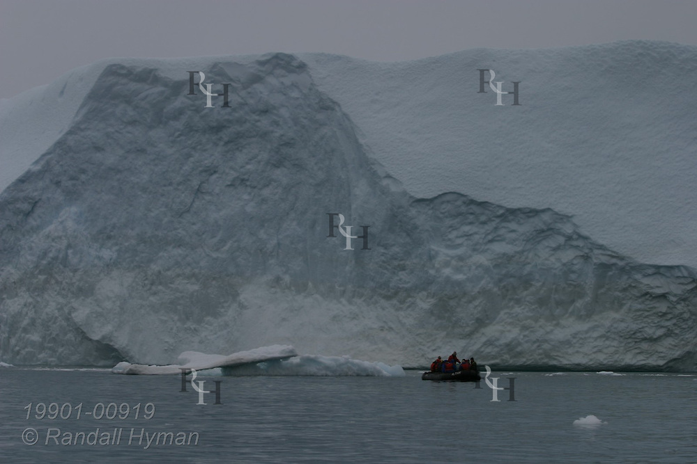Cruise ship passengers in rubber Zodiac raft are dwarfed by massive iceberg at Ilulissat Kangerlua Icefjord in Disko Bay, Greenland.