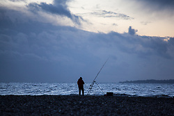 © Licensed to London News Pictures. 01/02/2014. Titchfield, Hampshire, UK. A fisherman fishing at dawn as storm clouds pass in the distance on what is set to be another stormy day, with more wet and windy weather forecast. Photo credit : Rob Arnold/LNP