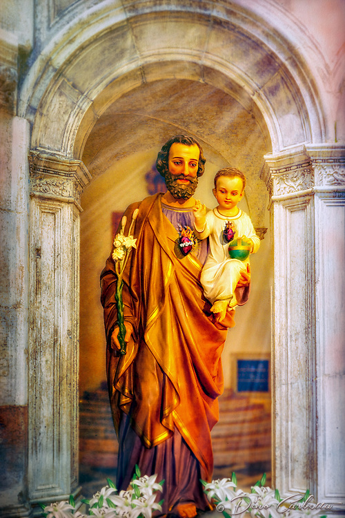"""""""Saint Joseph and Baby Jesus - Santa Maria Maggiore in Assisi and Venice - Painting by Dino Carbetta""""…<br /> <br /> The Church of Santa Maria Maggiore in Assisi is located outside the first city walls, in Piazza del Vescovado. It was the heart of the medieval bishop's citadel and center of religious power until the 11th century when it gave the title of the Cathedral to San Rufino. According to tradition, the first Cathedral of Assisi was built in this site close to the Roman city walls in the 4th century. The crypt under the apse of the present church, which is the oldest surviving part of the structure, seems to date to the 9th or 10th century. St. Francis was baptized in the temple. The interior has a basilica plan with three naves, separated by pillars. In the early Middle Ages, it was an episcopal residence. In 1035, at the time of Bishop Ugone, the title of Cathedral was transferred from Santa Maria Maggiore to the church of San Rufino, where the relics of the patron saint were kept. San Francesco was a guest of Bishop Guido I several times in the adjacent Palazzo Vescovile, in front of which he stripped off his clothes, nurturing a special bond with the church of Santa Maria Maggiore. A stone outside the apse bears witness to works carried out at the time of Francis and Bishop Guido in the year 1216. I found the ancient church to be uncomplicated, yet comforting and reverent. The primitive and recently discovered catacombs below, reveal its age and status throughout history. This image is a compilation painting of several images I combined from Assisi to Venice. Saint Joseph is the patron of the Universal Church. Here along with the young Christ, the painting reveals both Perfect and Sacred Hearts."""