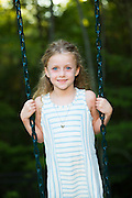 portrait of girl standing on swing