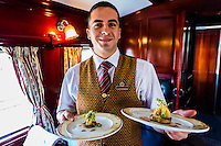 A waiter serving hearts of palm on grilled abergine in the pillared pre-1940s dining car on the luxury Rovos Rail train between Pretoria and Cape Town, South Africa.