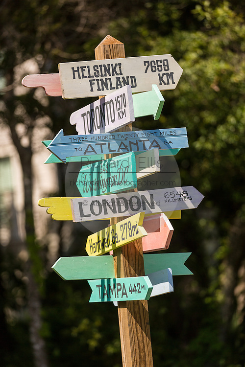 A directional sign pointing to world cities in Folly Beach, SC.