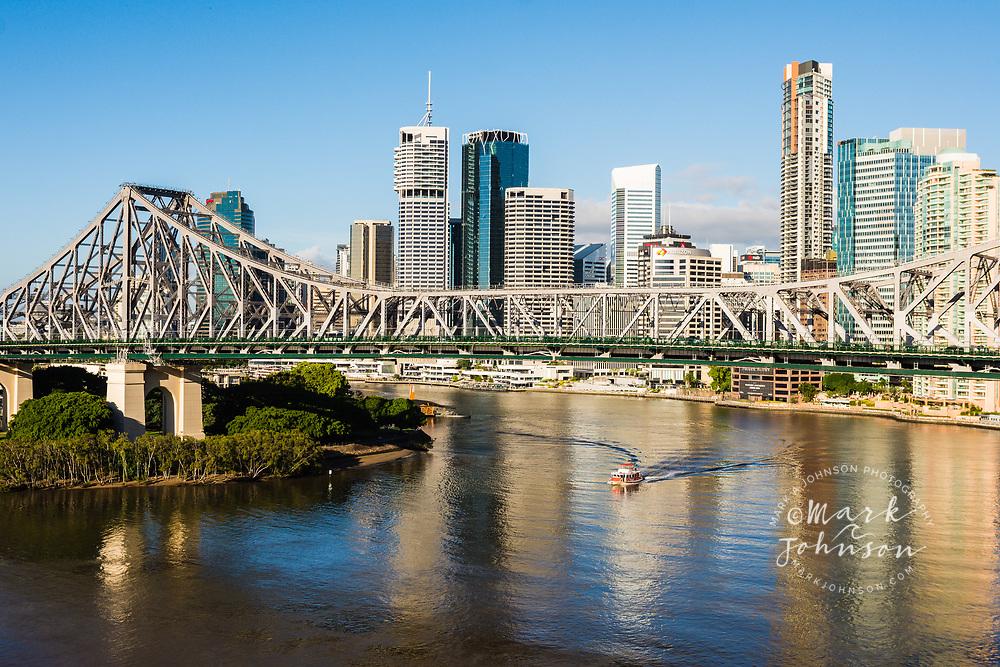 A city ferry passing under the Story Bridge, Downtown Brisbane behind, Queensland, Australia