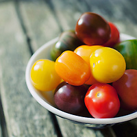 Rainbow tomatoes in a blue bowl on a wooden table
