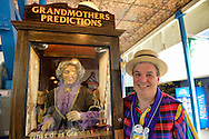 Brooklyn, New York, USA. 10th August 2013. BOB YORBURG, AKA Professor Phineas FeelGood the Magician, of Yorktown Heights, stands next to Grandmothers Predictions, the famous fortune telling game, during the 3rd Annual Coney Island History Day celebration. Yorburg restored Coney Island's Grandma after the game was seriously damaged during Hurricane Sandy in October 2012.