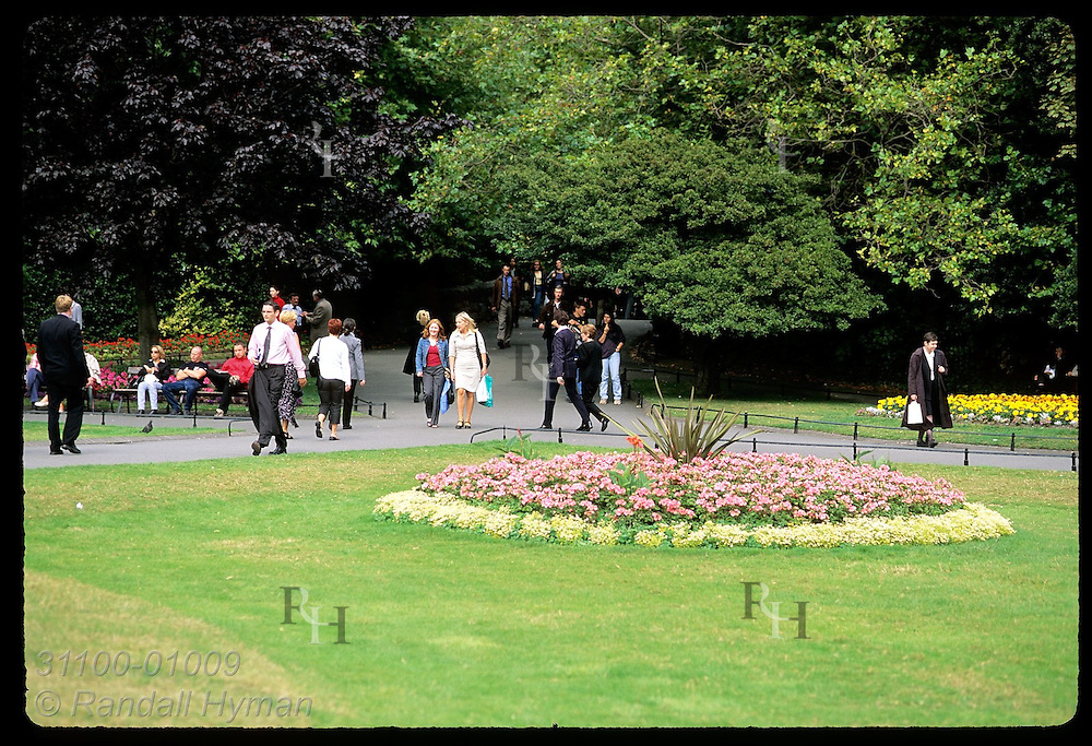 People walk and rest amid trees and flowers of St. Stephen's Green on a September afternoon; Dublin, Ireland.