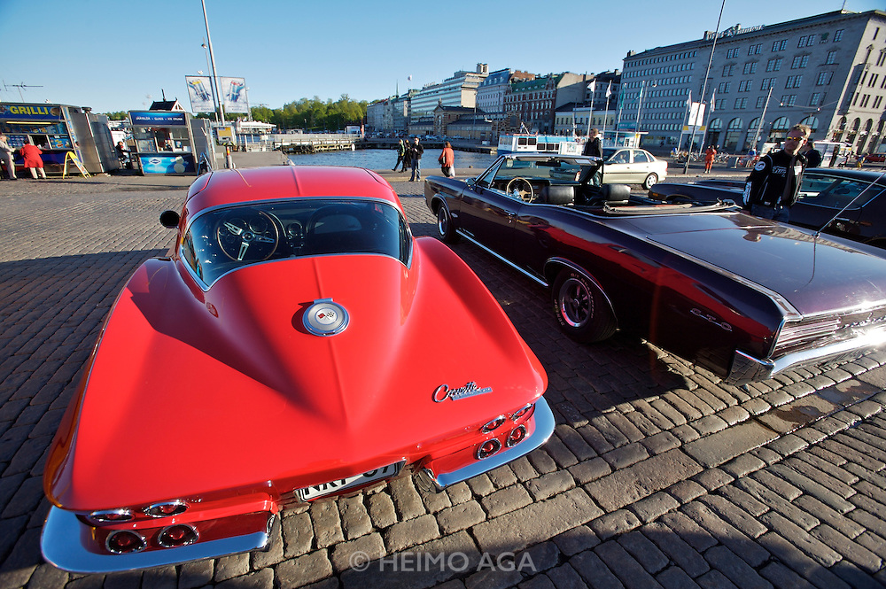 During summer from June to Septemper, every first Friday of the month is Vintage Car Cruising Night. Hundreds of classic American cars cruise around downtown Helsinki and meet at special places to have a good time, here at Kauppatori (Market Square), Uspenski orthodox cathedral in background. Sexiest beast of them all: Corvette Sting Ray Fastback Coupe?. Here next to a Plymouth Barracuda cabriolet (r.)