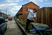 Drew Jonczak does some gardening in front of his home in Natrona, Pa. <br />