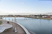 Nederland, Nijmegen, 24-2-2017 De bijna 4 km. lange nevengeul van de Waal bij Lent. Grootste onderdeel van de vele werken van Rijkswaterstaat om bij hoogwater een betere waterafvoer in de rivier te hebben. Het dorp veurlent is op een kunstmatig eiland komen te liggen met twee kleinere bruggen als ontsluiting. Een voetgangersbrug, de steltlopersbrug voor wandelaars naar het recreatiegebied. Ruimte voor de rivier, water, waal. In de nieuwe dijk wordt een drempel gebouwd die stapsgewijs water doorlaat en bij hoogwater overloopt. The Netherlands, Nijmegen Measures taken by Nijmegen to give the river Waal, Rhine, more space to flow during highwater and to prevent the risk of flooding. Room for the river. Reducing the level, waterlevel. Large project to create a new paralel gully, an extra flow of water, so the river can drain more water during highwater. Due to climate change and expected rise, increase of the sealevel, the Dutch continue to protect their land from the water. Foto: Flip Franssen