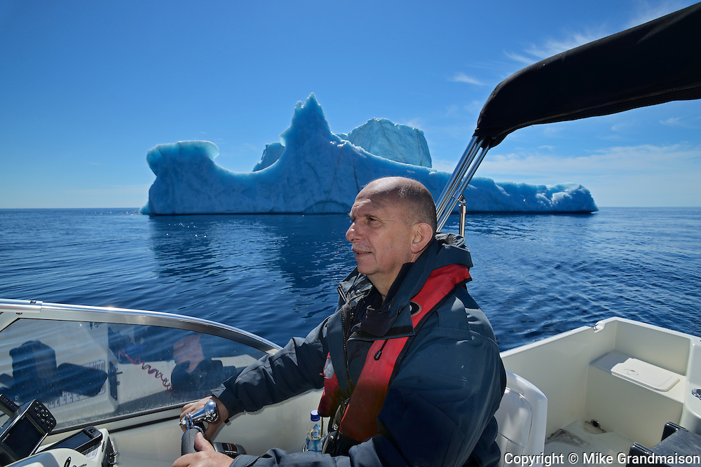 Tour guide Paul Dunphy in front of a large iceberg 6 miles in the Atlantic Ocean<br /> St. Anthony<br /> Newfoundland & Labrador<br /> Canada