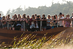 © Licensed to London News Pictures. 18/07/2014. Southwold, UK.   Fans line the riverside to watch Lily Allen recording a special live performance for the Andrew Marr Show from The Latitude Festival on a riverside stage.   Lily Allen replaced Two Door Cinema Club as tonight's headline act - this was announced earlier this week as a result of Two Door Cinema Club's frontman Alex Trimble's ill health.  It was reported Trimble collapsed at an american airport.  Latitude is British annual music festival.  Photo credit : Richard Isaac/LNP