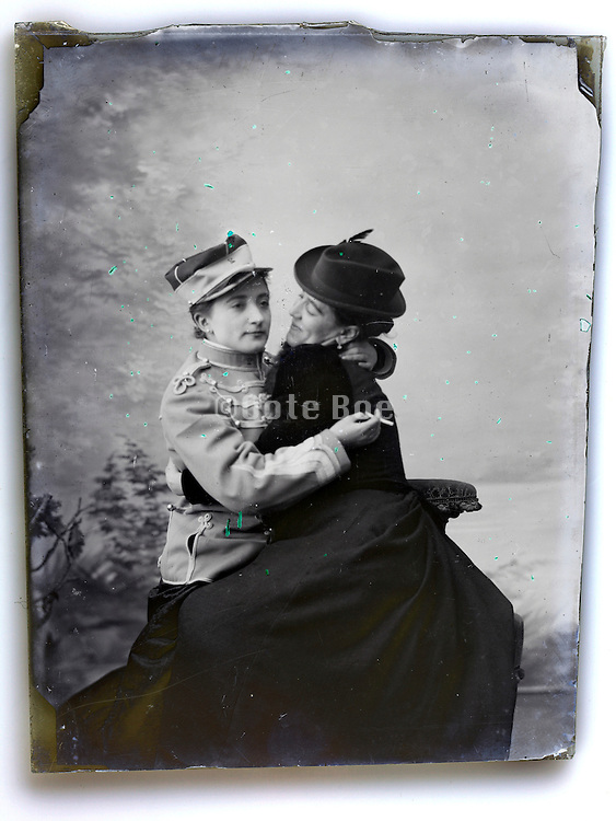 two woman dressed as soldier and lover embrasing each other 1900s studio portrait