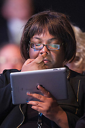 © Licensed to London News Pictures . 23/09/2013 . Brighton , UK . MP for Hackney North and Stock Newington , DIANE ABBOTT , on her iPad in the audience during the Work and Business session . Day 2 of the Labour Party 's annual conference in Brighton . Photo credit : Joel Goodman/LNP