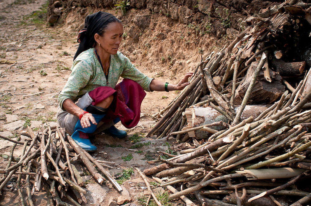 A woman sorts sticks according to size and shape. These will be used for building fires in the kitchen for cooking.