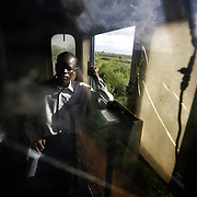 "Alloyce Ojiambo, the co-driver of the train from Nairobi to Mombasa, in the engine car with cracked windows of the Nairobi-Mombasa train. Also known as the ""Lunatic Express"", It was the railway line that built Kenya, linking the port town of Mombasa through the capital, Nairobi, to the shores of Lake Victoria and on to the Ugandan capital, Kampala. It cost $5m (in 1894 money) and countless workers died during its construction. There were derailments, collisions, tribal raids and attacks by lions. Yet despite becoming one of Kenya's national treasures and a vital economic artery for east Africa, the railway now lies in a state of disrepair. A South African consortium has taken it over and plans to invest millions, returning it to its former glory. But there has been a row over the railway's financing which may yet derail the .project. .."