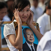 A mourner covers her ears as cannons are fired during funeral services for the former Cambodian King Norodom Sihanouk  Friday Feb. 1, 2013 in Phnom Penh, Cambodia.  The cremation of the former king is set for Feb. 4, 2013.  Sihanouk died last October 15, 2012, in Beijing, China.  He was 89 years old.