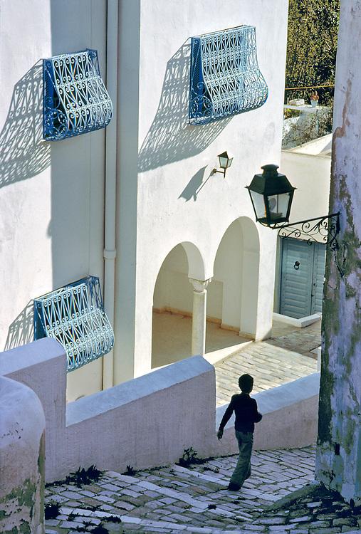 A man walks beside a whitewashed building in Sidi Bou Said, Tunisia.