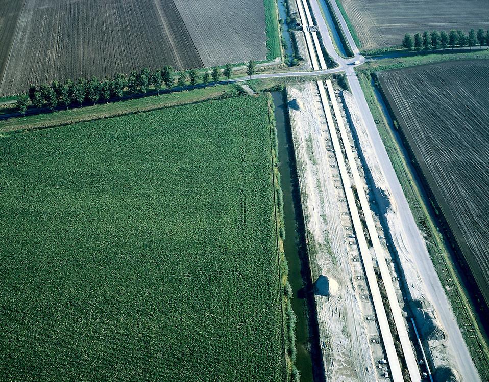 Nederland, Zuid-Holland, Hoeksche Waard, 17-10-2003;  aanleg HSL, de hogesnelheidslijn doorsnijdt het polderlandschap, links en rechts van de nieuwe spoorbaan de spoorsloten, rechts de werkweg; de baan zelf bestaat uit een zogenaamde zettingsvrije plaat: deze dubbel uitgevoerde betonnen plaat is gefundeerd op heipalen, de spoorstaven worden direkt op deze plaat aangebracht (dus zonder dwarsliggers (bielzen) in ballastbed); verkeer en vervoer, transport, infrastructuur, bouwen, spoor, rail, planologie ruimtelijke ordening, landschap;luchtfoto (toeslag), aerial photo (additional fee)<br /> foto /photo Siebe Swart