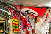 16 FEBRUARY 2013 - BANGKOK, THAILAND:   A flag vendor sets up his stall in the Chatuchak Weekend Market in Bangkok. Chatuchak Weekend Market in Bangkok is reportedly the largest market in Thailand and the world's largest weekend market. Frequently called J.J., it covers more than 35 acres and contains upwards of 5,000 stalls.    PHOTO BY JACK KURTZ