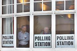 © Licensed to London News Pictures.  15/11/2012. ASTON CLINTON, UK. Presiding Officer Peter Western (pictured left) looks out of the window as he waits for voters in the Police & Crime Commissioner elections (PCC) for the Thames Valley region. By 11am just 30 people had voted at this polling station and nationally turnout is expected to be very low. Photo credit :  Cliff Hide/LNP