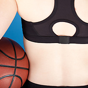 A woman in shorts and a sports bra holding a basketball, seen from behind.