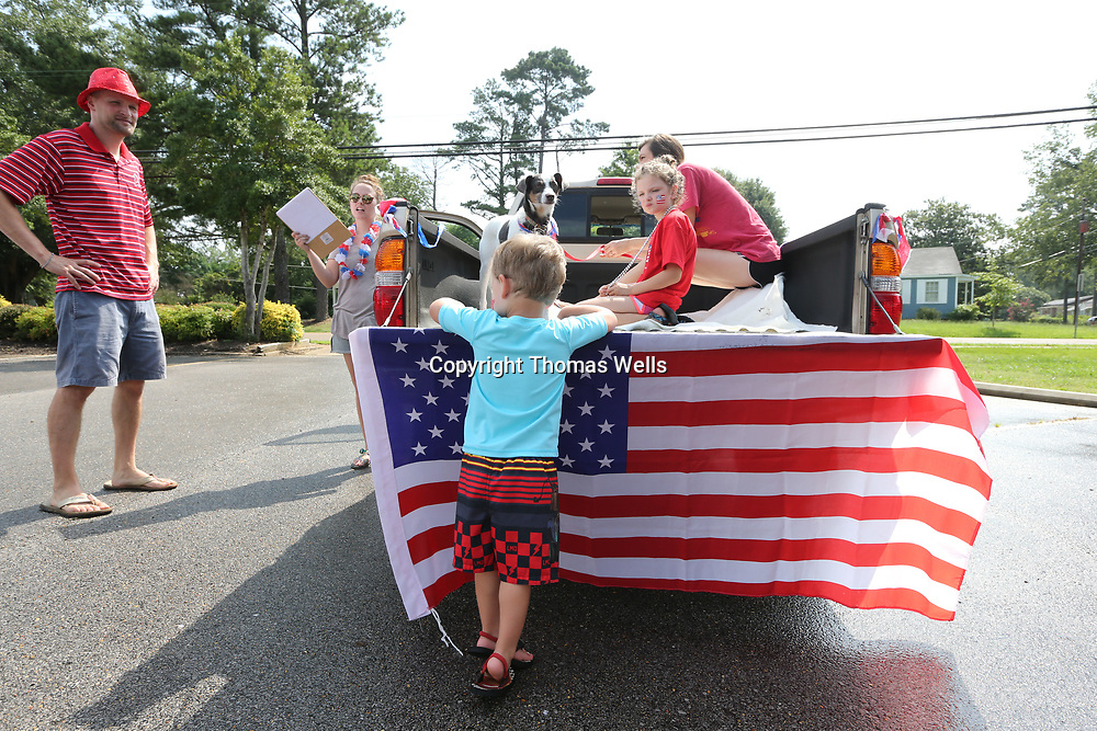 Arthur Frazier, 4, leans against the tailgate of his dad's truck with the Ameican flag attached to it before Tuesday annual Joyner Neighborhood parade.