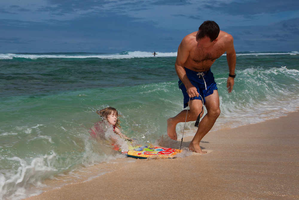A father pulls his little girl on a boogie board as a wave sweeps over her on the beach in Hawaii
