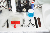 Scissors combs razor brush and hair products on counter in barber shop