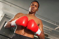 Boxer with red boxing gloves in gym half length