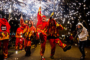 "Sergi Ventura Solsona, center, and Dani Calduch, second from right, both of Barcelona, Spain, celebrate the Festa Major de Sant Antoni in the Eixample district of Barcelona. The festival ends with a ""correfoc"" or fire run, where participants dressed as devils dance and shoot fireworks in the street."