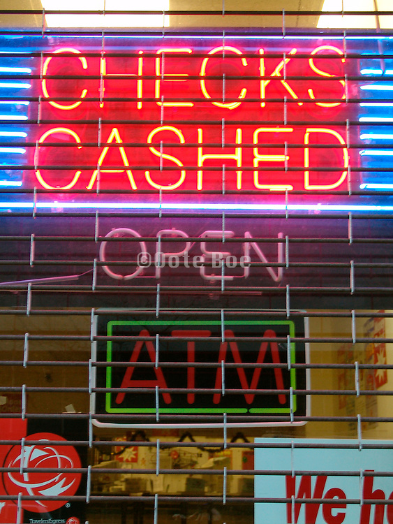 Checks cashing neon advertising sign hanging in the window of a money shop.