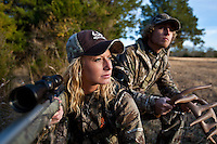 Man and woman deer hunter rattling for deer and shooting a muzzleloader with a scope