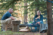 Couple enjoying cooking over a campfire, McCall, Idaho. MR