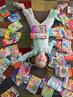 Girl lying on library floor with books scattered around view from above