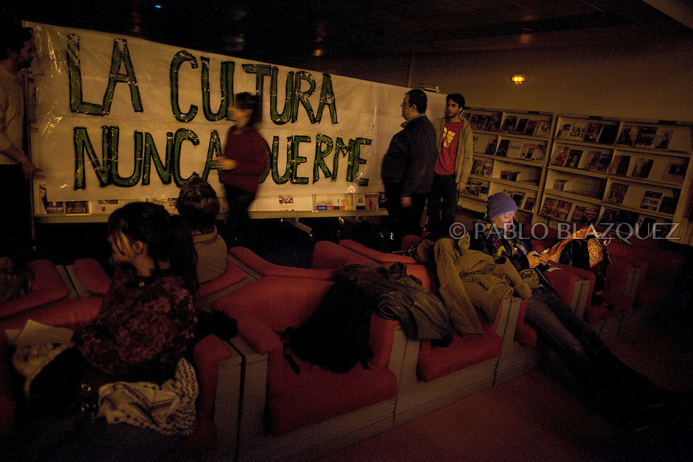 Student and other protesters occupy El Retiro Library to ask Madrid Regional Government to open libraries 24 hours a day during exams time on December 23, 2013. Banner reads 'Culture never sleeps'. The Madrid regional Government is cutting opening hours for Public Libraries, as a expending cuts measure. Students were allowed to stay overnight in El Retiro library, but lights were turned off so they couldn't study.