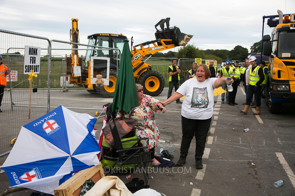 13 local activists locked themselves in specially made arm tubes to block the entrance to Quadrilla's drill site in New Preston Road, July 03 2017, Lancashire, United Kingdom. Michellemartin and friend left behind police lines amongst the demolition. The 13 activists included 3 councillors; Julie Brickles, Miranda Cox and Gina Dowding and Nick Danby, Martin Porter, Jeanette Porter,  Michelle Martin, Louise Robinson,<br /> Alana McCullough, Nick Sheldrick, Cath Robinson, Barbara Cookson, Dan Huxley-Blyth. The blockade is a repsonse to the emmidiate drilling for shale gas, fracking, by the fracking company Quadrilla. Lancashire voted against permitting fracking but was over ruled by the conservative central Government. All the activists have been active in the struggle against fracking for years but this is their first direct action of peacefull protesting. Fracking is a highly contested way of extracting gas, it is risky to extract and damaging to the environment and is banned in parts of Europe . Lancashire has in the past experienced earth quakes blamed on fracking.