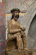 Le Christ aux outrages, sculpture in polychrome wood, 16th century, depicting Christ, hands bound and wearing the crown of thorns, waiting for crucifixion after being beaten and humiliated, in the chevet of the Cathedral Saint-Samson, begun in the 13th century on the site of an older church and completed in the 18th century, in Dol-de-Bretagne, Brittany, France. The cathedral is dedicated to one of the founding saints of Brittany and until 1801 was the seat of the archbishopric of Dol. Picture by Manuel Cohen