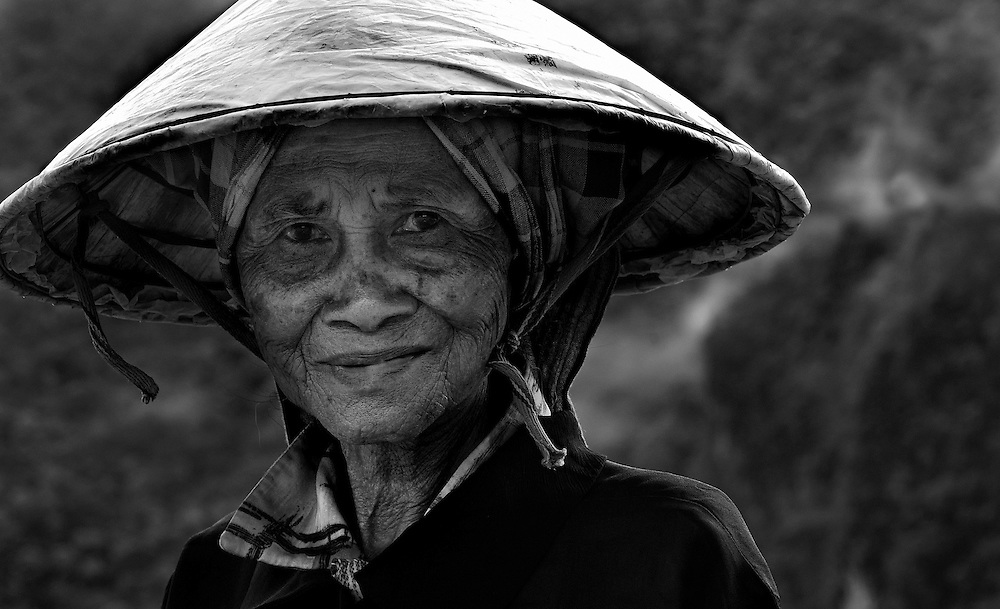 An old woman still works in the rice field at Tham Lot Khong Lo, Laos.