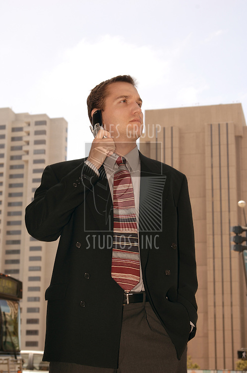 Business executive on a cell phone outside in the heart of the city