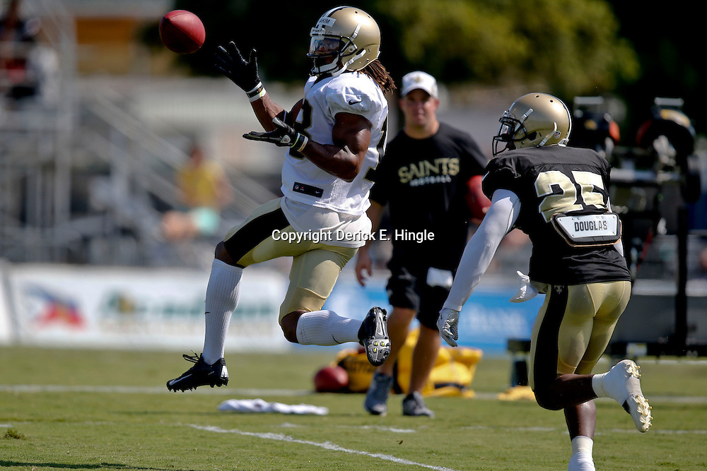 Jul 29, 2013; Metairie, LA, USA; New Orleans Saints wide receiver Saalim Hakim (18) catches a pass ahead of defensive back Rafael Bush (25) during a morning training camp practice at the team facility.  Mandatory Credit: Derick E. Hingle-USA TODAY Sports