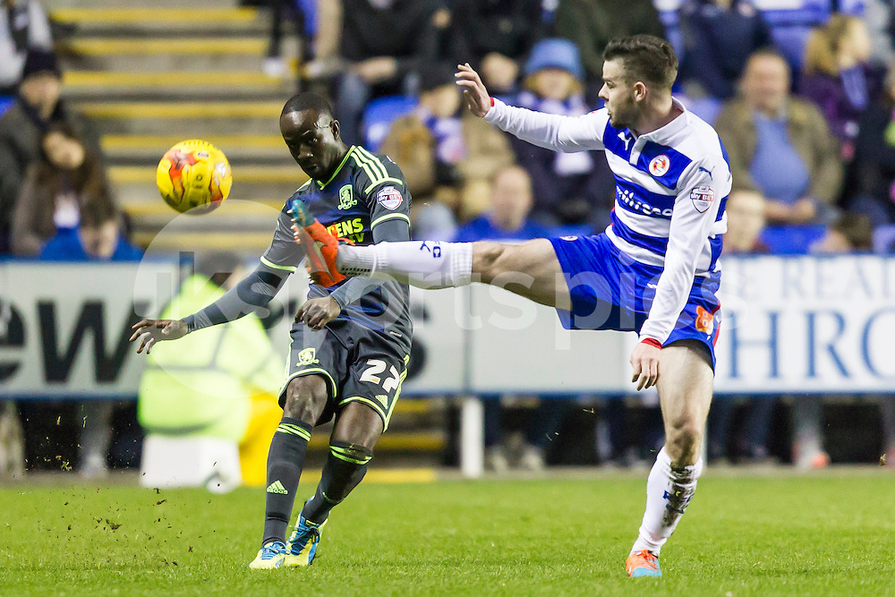 Albert Adomah of Middlesbrough plays the ball while coming under pressure by Danny Guthrie of Reading  during the Sky Bet Championship match between Reading and Middlesbrough at the Madejski Stadium, Reading, England on 10 January 2015. Photo by Gareth  Brown.
