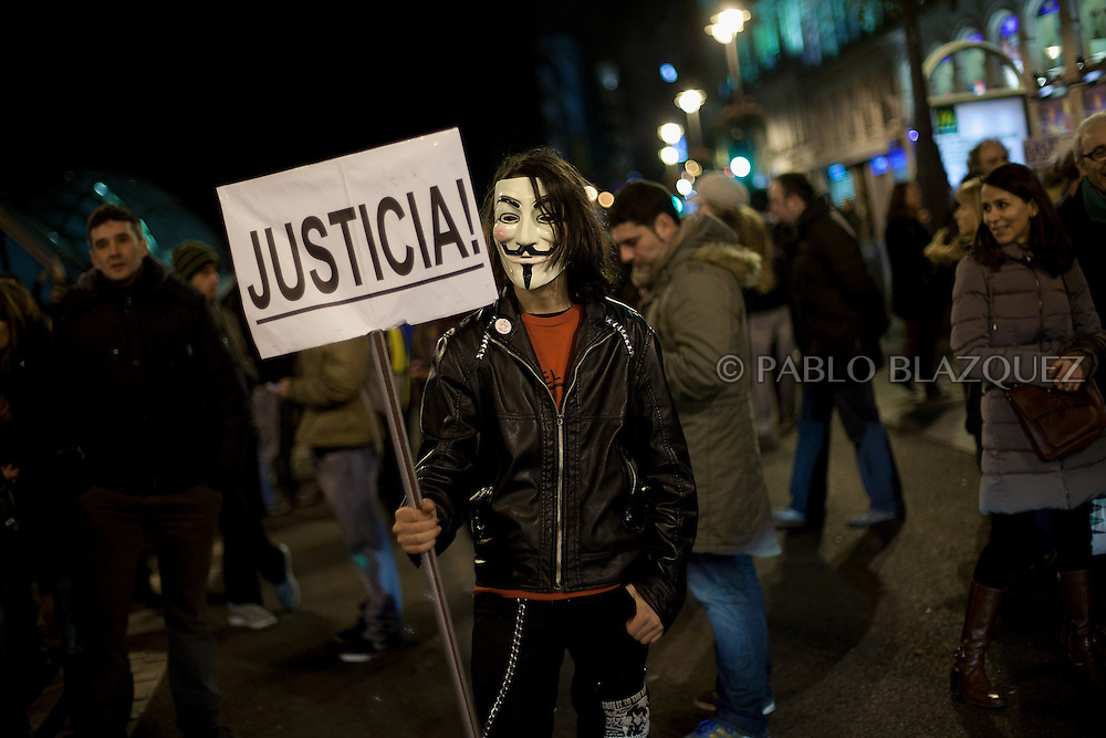 A protester wearing a guy fawkes mask and holds a placard reading 'Justice' during a demonstration against political corruption and claiming Mariano Rajoy to resign in Madrid on February 1, 2013. The Spanish Newspaper 'El Pais' published secret papers of income implicating Spanish Prime Minister and other members of the PP (Popular Party). Rajoy's government has denied these secret payments.