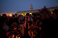 Protesters clap and sing in the main square of Tabrurk demanding Qadaffi to leave on Feb. 24, 2011. The square has become a symbol of New Libya, tents have been set up, people are giving out free food, and heavy equiptment is being used to repair the square.
