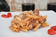 alla buttera penne pasta side view from left close-up on white dish, italian food of Maremma Tuscany