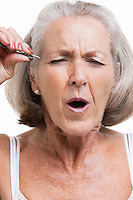 Senior woman tweezing eyebrows against white background